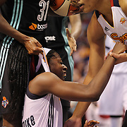 Chiney Ogwumike, (below), Connecticut Sun, the WNBA number one draft pick making her WNBA debut, pump fakes and draws the foul as she is hit hard by Tina Charles, New York Liberty, the former Sun player during the Connecticut Sun Vs New York Liberty WNBA regular season game at Mohegan Sun Arena, Uncasville, Connecticut, USA. 16th May 2014. Photo Tim Clayton