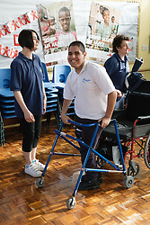 Boy with cerebral palsy preparing to use walking aid,
