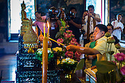 12 APRIL 2014 - BANGKOK, THAILAND: Deputy Bangkok Governor Police General ASAWIN KWANMUANG lights a candle and offers a prayer before the procession for the Phra Buddha Sihing at the start of Songkran in Bangkok. The Phra Buddha Sihing, a revered statue of the Buddha, is carried by truck through the streets of Bangkok so people can make offerings and bathe it in scented oils. Songkran is celebrated in Thailand as the traditional New Year's from 13 to 16 April. The date of the festival was originally set by astrological calculation, but it is now fixed. The traditional Thai New Year has been a national holiday since 1940, when Thailand moved the first day of the year to January 1. The first day of the holiday period is generally the most devout and many people go to temples to make merit and offer prayers for the new year.    PHOTO BY JACK KURTZ