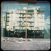 The reflection of a typical 1960's Athenian building on a bank's broken front glass in Alexandras avenue, Athens. <br /> <br /> Following the murder of a 15 year old boy, Alexandros Grigoropoulos, by a policeman on 6 December 2008 widespread riots, protests and unrest followed lasting for several weeks and spreading beyond the capital and even overseas<br /> <br /> When I walked in the streets of my town the day after the riots I instantly forgot the image I had about Athens, that of a bustling, peaceful, energetic metropolis and in my mind came the old photographs from WWII, the civil war and the students uprising against the dictatorship. <br /> <br /> Thus I decided not to turn my digital camera straight to the destroyed buildings but to photograph through an old camera that worked as a filter, a barrier between me and the city.