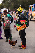 A reveler wearing traditional Cajun Mardi Gras costume walks a chicken on a leash during the Courir de Mardi Gras chicken run on Fat Tuesday February 17, 2015 in Eunice, Louisiana. Cajun Mardi Gras involves costumed revelers competing to catch a live chicken as they move from house to house throughout the rural community.