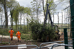 Wendover, UK. 4th May, 2021. Tree surgeons working on behalf of HS2 Ltd use heavy machinery close to a security fence to clear ancient woodland at Jones Hill Wood in the Chilterns AONB for the HS2 high-speed rail link. Felling of the woodland, which contains resting places and/or breeding sites for pipistrelle, barbastelle, noctule, brown long-eared and natterer's bats and is said to have inspired Roald Dahl's Fantastic Mr Fox, recommenced after a High Court judge refused an application for judicial review and lifted an injunction.