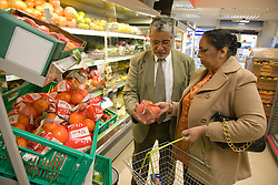 Older couple selecting fruit in a supermarket,