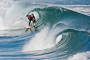Surfer at St. Clair's Beach in New Zealand, coming out barrel #1 and looking down barrel #2.
