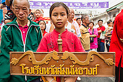 """10 FEBRUARY 2013 - BANGKOK, THAILAND:  A Thai girl carries a banner announcing the name of troupe of Lion Dancers during Chinese New Year on Yaowarat Road in Bangkok. Bangkok has a large Chinese emigrant population, most of whom settled in Thailand in the 18th and 19th centuries. Chinese, or Lunar, New Year is celebrated with fireworks and parades in Chinese communities throughout Thailand. The coming year will be the """"Year of the Snake"""" in the Chinese zodiac.   PHOTO BY JACK KURTZ"""