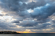 Bondi Beach Sunrise with dramatic clouds and early morning surfers in the water
