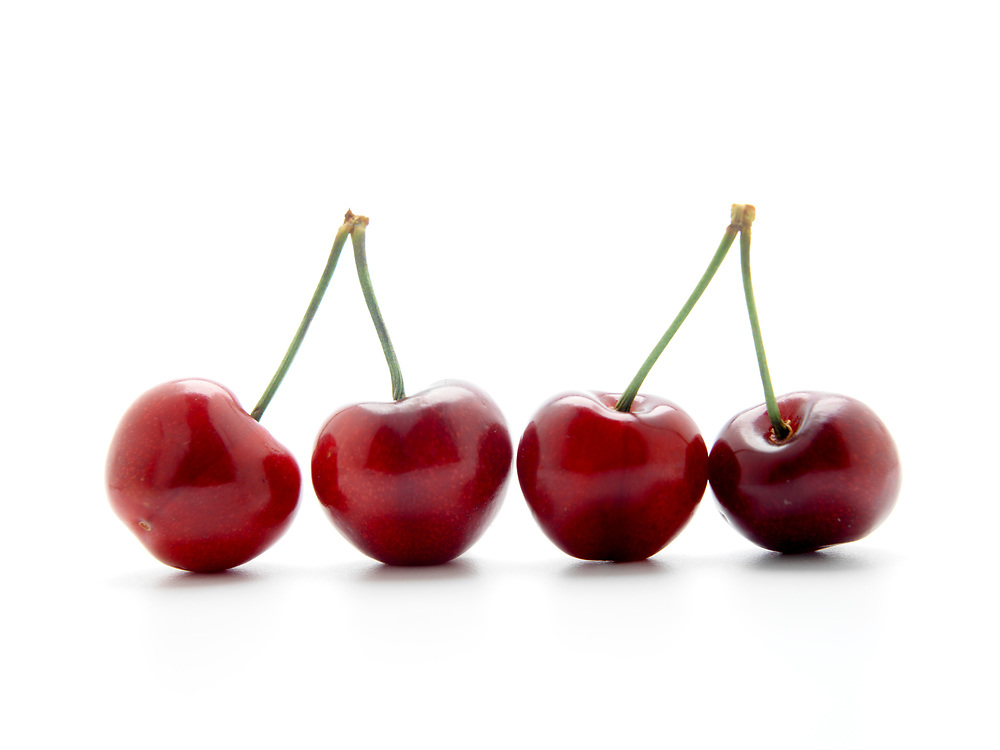 4 fresh red cherries in a line with long stems on a white background