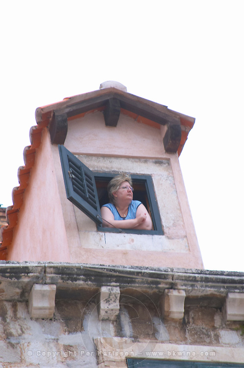 A woman looking out a rooftop roof top window in an old house on the main Placa street Dubrovnik, old city. Dalmatian Coast, Croatia, Europe.