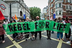 © Licensed to London News Pictures. 23/08/2021. LONDON, UK.  Climate activists from Extinction Rebellion with a banner outside Leicester Square tube station during a protest in Covent Garden.  The group has announced that it will stage protests in the capital for the next two weeks as they try to raise awareness of the effects of big business on climate change.  Photo credit: Stephen Chung/LNP