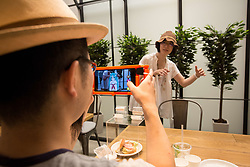 July 8, 2017 - Sendai, Miyagi-ken, Japan - SENDAI, JAPAN - JULY 8: Anime fans holding a smart phone equipped with augmented reality (AR) application takes photo with her virtual idol Hatsune Miku while having some sweets during an event in Sendai, Japan on July 8, 2017. As part of a promotion with telecommunications provider au/KDDI, Crypton Future Media and Blue Leaf Cafe operator, guest can enjoy dining with a special menu with their Vocaloid superstarIdol Hatsune Miku several days. (Photo by Richard Atrero de Guzman/NUR Photo) (Credit Image: © Richard Atrero De Guzman/NurPhoto via ZUMA Press)