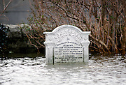 Deep flooding nearly covers gravestone in Towyn in North Wales, UK