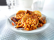 Baked beans and sausages on crumpets stock photos