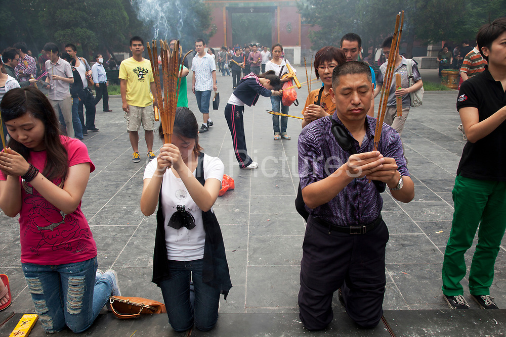 """People come to pray and burn incense sticks at The Yonghe Temple, also known as the """"Palace of Peace and Harmony Lama Temple"""", the """"Yonghe Lamasery"""", or - popularly - the """"Lama Temple"""" is a temple and monastery of the Geluk School of Tibetan Buddhism located in the northeastern part of Beijing, China. It is one of the largest and most important Tibetan Buddhist monasteries in the world. The building and the artworks of the temple is a combination of Han Chinese and Tibetan styles."""