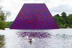 Artist Christo unveils his 20m high installation on The Serpentine made from over 7000 barrels, titled The Mastaba, which will be on the Serpentine until 23 September 2018. The Installation is comprised of 7,506 horizontally stacked barrels. It is 20m high, 30m wide and 40m long. Hyde Park, London, June 18 2018.