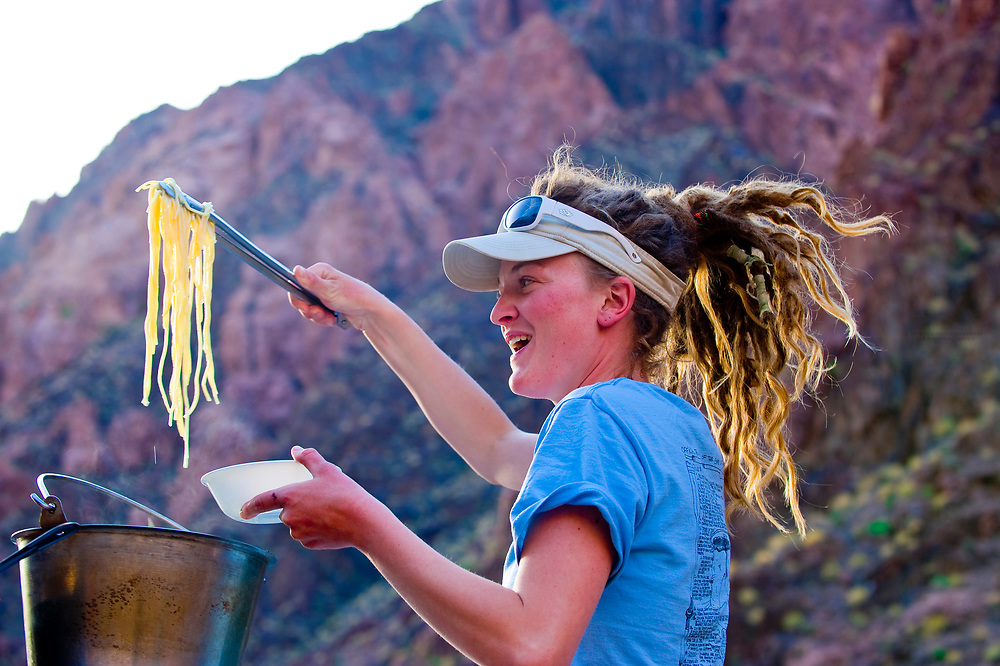 """River guide Amanda LaRiche cooking spaghetti, Camping at """"Cremation"""", Whitewater rafting trip (oar trip) on the Colorado River in Grand Canyon, Grand Canyon National Park, Arizona USA"""