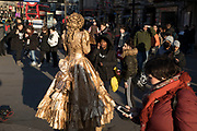 Girls try to distract a gold living statue street performer in Piccadilly Circus in London, England, United Kingdom.