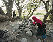 Niso, a Wakhi woman, walks past a pre-islamic shrine, called Chilkan.  The traditional life of the Wakhi people, in the Wakhan corridor, amongst the Pamir mountains.