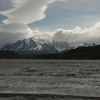 Wind-driven lenticular clouds hover above Lago Amarga, The Towers of Paine & Monte Almirante Nieto in Torres del  Paine National Park in Patagonia, Chile.