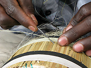 Members of the Guardians of Hope, a program set up by the AEBR and CBM.(Association des Eglises Baptistes au Rwanda and Canadian Baptist Ministries) for people affected with HIV/AIDS, make traditional Rwandan baskets to sell to support themselves.
