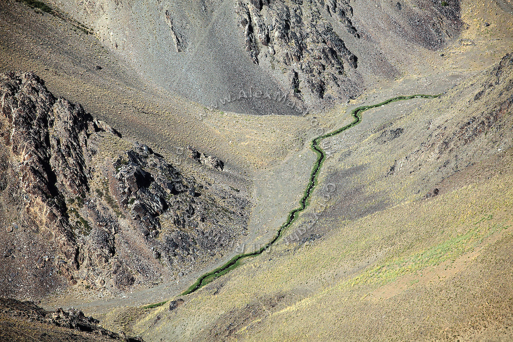 A small river running through the Hindu Kush, the mountain range crossing Afghanistan and separating Kabul from Bamiyan, is photographed from a UNAMA helicopter on its way to the capital. The Buddhas of Bamiyan were two 6th century monumental statues of standing Buddhas carved into the side of a cliff in the Bamiyan valley in the Hazarajat region of central Afghanistan, situated 230 km northwest of Kabul at an altitude of 2500 meters. The statues represented the classic blended style of Gandhara art. The main bodies were hewn directly from the sandstone cliffs, but details were modelled in mud mixed with straw, coated with stucco. Amid widespread international condemnation, the smaller statues (55 and 39 meters respectively) were intentionally dynamited and destroyed in 2001 by the Taliban because they believed them to be un-Islamic idols.  Once a stopping point along the Silk Road between China and the Middle East, researchers think Bamiyan was the site of monasteries housing as many as 5,000 monks during its peak as a Buddhist centre in the 6th and 7th centuries. It is now a UNESCO Heritage Site since 2003. Archaeologists from various countries across the world have been engaged in preservation, general maintenance around the site and renovation. Professor Tarzi, a notable An Afghan-born archaeologist from France, and a teacher in Strasbourg University, has been searching for a legendary 300m Sleeping Buddha statue in various sites between the original standing ones, as documented in the old account of a renowned Chinese scholar, Xuanzang, visiting the area in the 7th century. Professor Tarzi worked on projects to restore the other Bamiyan Buddhas in the late 1970s and has spent most of his career researching the existence of the missing giant Buddha in the valley.