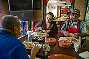 Restaurant owner Lourdes Alvarez having breakfast with her father and uncle at her family's restaurant, Dos Loredos, in Chicago, Illinois.  (Lourdes Alvarez is featured in the book What I Eat;  Around the World in 80 Diets.)