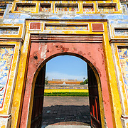 A colorful gate to the Dien Tho Residence at the Imperial City in Hue, Vietnam. A self-enclosed and fortified palace, the complex includes the Purple Forbidden City, which was the inner sanctum of the imperial household, as well as temples, courtyards, gardens, and other buildings. Much of the Imperial City was damaged or destroyed during the Vietnam War. It is now designated as a UNESCO World Heritage site.