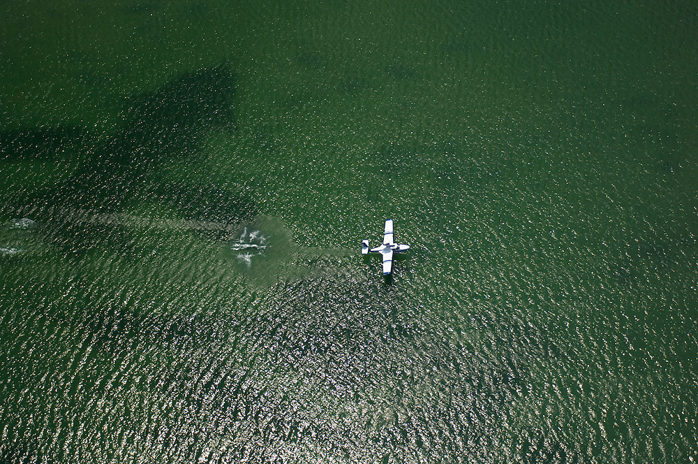 A seaplane is seen from above as it lands on Lake Superior in the bay of Grand Marais Michigan during an annual seaplane gathering.
