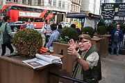Flamboyant older gentleman wearing flip up sunglasses on his spectacles gesticulates to people he is chatting to while enjoying a pint of beer outside a pub at Liverpool Street Station in the City of London, England, United Kingdom.