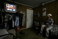 On his day off, migrant worker Laurencio Garcia, 61, of Hidalgo, Mexico watches a gameshow in a friends room. Garcia is married with two children and has worked at Titan Farms for three years.