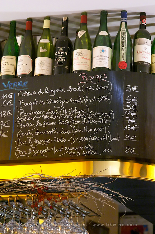 A blackboard chalkboard black chalk board with the wine list with wines served by the glass (Vins Au Verre), Coteaux du Languedoc, Bourgogne, Chorey les Beaune, Gevrey Chambertin, with a selection of exclusive bottles on the shelf that has been drunk in the wine bar winebar at the restaurant Le Gourmandin in Beaune Cote d'Or Burgundy Bourgogne France Europe