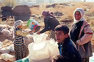 Women and children store grain for the animals in Catal Ko?y, a former village guard village near Diyarbakir in eastern Turkey.