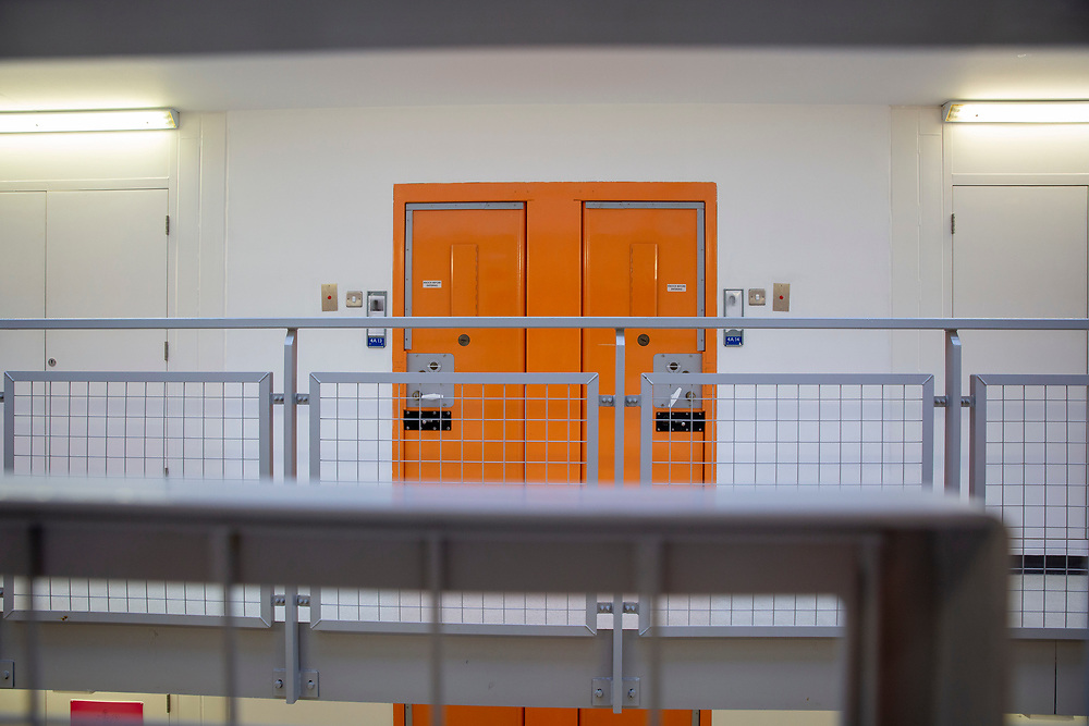 Two orange cell doors on a wing inside HMP Bronzefield, a private prison run by Sodexo Justice Services on the outskirts of Ashford in Middlesex, United Kingdom. HMP Bronzefield is an adult and young offender female prison, the only purpose built private prison solely for women in the UK and is the largest female prison in Europe. (photo by Andy Aitchison)