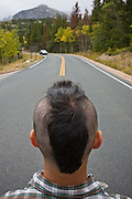 A young man with a mohawk stands in the middle of a road in Rocky Mountain National Park, Colorado.