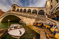 People sitting at outdoor cafe beneath the Rialto bridge, Grand Canal, Venice, Italy.