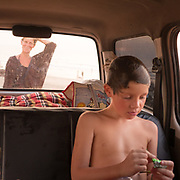 A mother returns to her camping van while her sons wait inside.