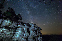 The milky way shines in the dark skies behind a cliff at Garden of the Gods, Illinois. I used a flashlight to light paint the cliffs from an angle, which created shadows and texture. The sky was a bit hazy which made the stars a little less clear.<br /> <br /> Date Taken: July 22, 2014