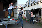 Sam Deome, 20, left, and her sister Emma, 17, middle, jump down from their moving truck as Justin Loomis, right, and Jay Hottle, obscured, help move furniture in to the house at Green Acres farm in South Randolph, Vt., Friday, May 20, 2016. The entire Deome family, including five siblings and their parents, moved from Montrose, Penn. to take over the farm from Craig and Joan Wortman. (Valley News - James M. Patterson) Copyright Valley News. May not be reprinted or used online without permission. Send requests to permission@vnews.com.