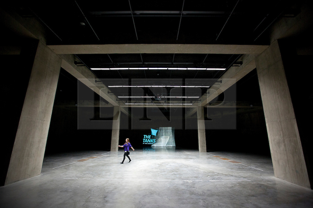 © Licensed to London News Pictures. 16/07/2012.  LONDON, UK. A member of Tate Modern staff walks across one of the gallery's new Tank Room exhibition spaces in London today (16/07/12). The new rooms, unveiled today mark the first phase of the Tate Modern Project and the beginning of the 15 week 'Art in Action' festival. Photo credit: Matt Cetti-Roberts/LNP