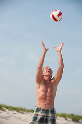 Athletic older man playing volleyball at the beach