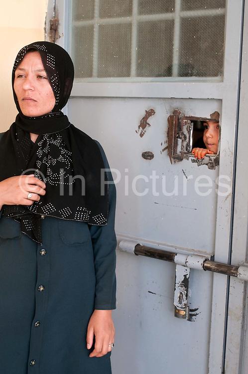 Afghanistan. Herat Women's prison - warder standing next to locked door
