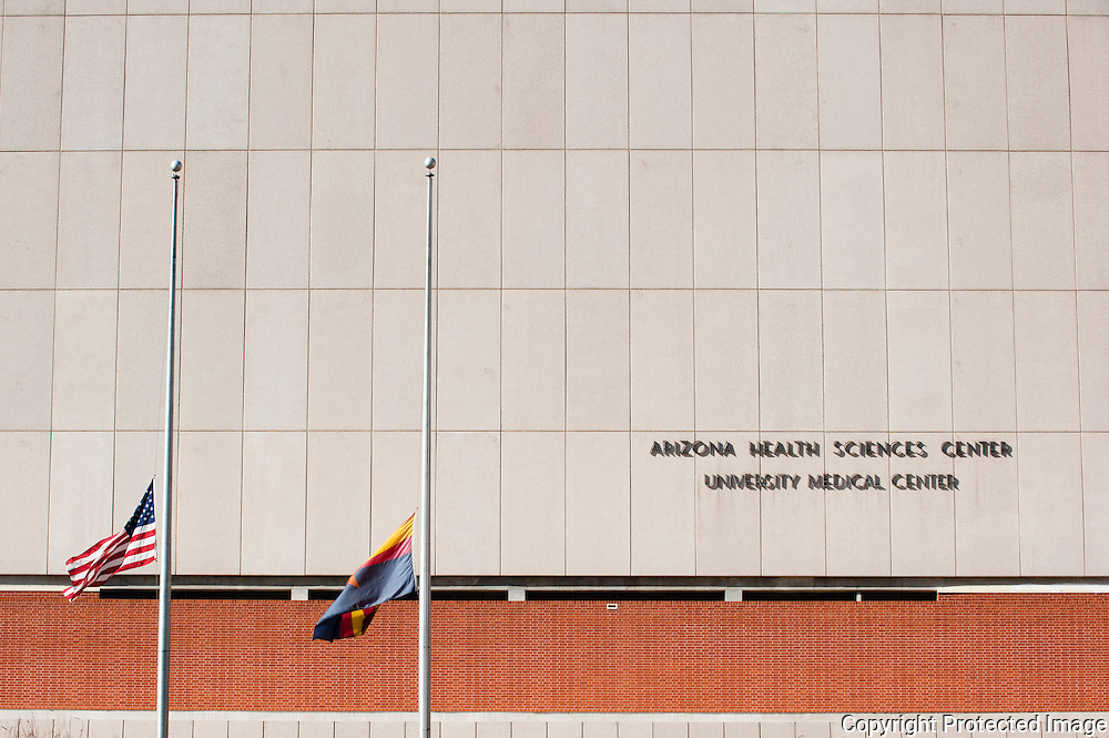 The US and State of Arizona flags flown at half staff in fron of the Arizona Health Sciences Center. Located at the memorial in front of the University of Arizona Medical Center in Tucson, Arizona. The memorial was placed for the victims of the recent shooting in Tucson.