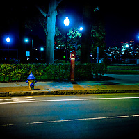 Lonely night scene with a car passing a lone fire hydrant with lights glowing in the background.