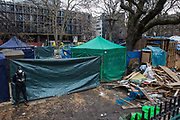 A National Eviction Team bailiff guards a protest camp in Euston Square Gardens previously occupied by environmental activists from anti-HS2 campaign group HS2 Rebellion on 6th February 2021 in London, United Kingdom. Bailiffs have been working on behalf of HS2 Ltd for the past eleven days to try to remove activists from tunnels dug by them beneath the site in order to seek to protect its trees from felling in connection with the HS2 high-speed rail project.