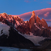 Golden mountain peak and pink sky light up with first light upon Cerro Torre in Patagonia, Argentina.