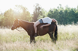 Young woman lying on her horse in farm and smiling, Bavaria, Germany