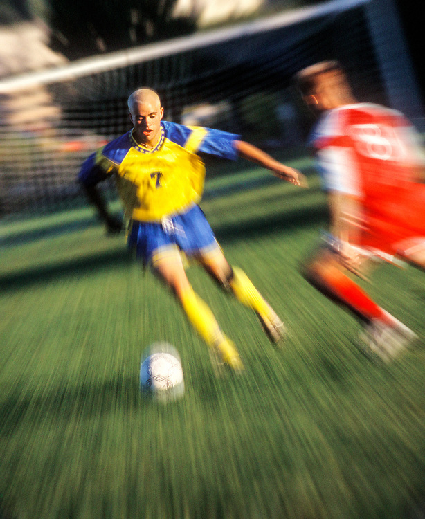 Two young men playing soccer.  Blur / zoom effect.
