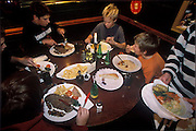 Friends and family celebrate Josh Bainton's 14th birthday party (he's at center) on Saturday night at The Crown, the neighborhood pub. (Supporting image from the project Hungry Planet: What the World Eats.) The Bainton family of Collingbourne Ducis, Wiltshire, England, is one of the thirty families featured, with a weeks' worth of food, in the book Hungry Planet: What the World Eats.