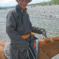 MONGOLIA. Herder guides geotourists across river during horseback ride in Darhad Valley.