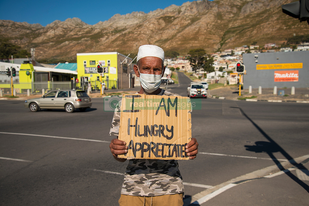 """Llewellenlyn Welgemoed, 63, stands on a street corner in Gordon's Bay, in the Western Cape, asking for food, Saturday, April 18, 2020. Welgemoed is a pensioner, who supports his wife and four kids. Normally he supplements his pension by working as a painter. <br /> """"They call me Taliban,"""" he says. """"I'm a qualified painter in Gordon's Bay,"""" he says. <br /> But as South Africa is lockdown in response to the Coronavirus, he's not allowed to work. It's also not allowed to stand outside and beg like this, the police has told him several times, Welgemoed explains. The fine is R2500, he adds.   <br /> Welgemoed gets a R1860 pension each month. He is grateful for the money, but says it's not enough to support his family. """"I must buy food. I must the rent,"""" he says. """"All my kids live on my pension. They're still in school. I'm the only breadwinner,"""" he says. """"My wife, she works at home. …<br /> """"I'm glad about what I get from the government,"""" he says. """"But here are six people at home and there is no food in the house."""" PHOTO: EVA-LOTTA JANSSON"""