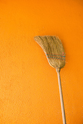 Broom leaning against yellow wall, Austria